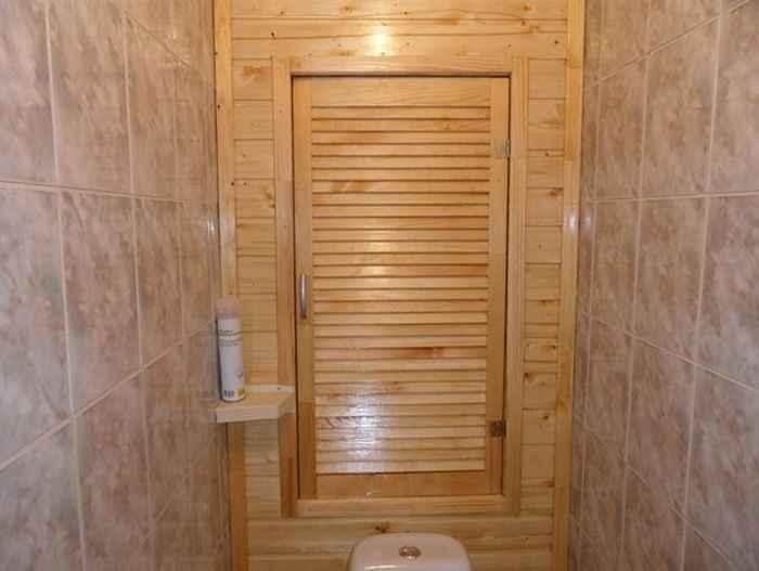 Деревянная дверь в шкафу в туалете квартиры